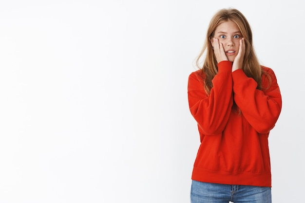 Femme choquée regardant avec empathie un ami racontant de terribles nouvelles en pressant les paumes contre les joues serrant les dents et haletant inquiet, se sentant nerveux et concerné, portant un joli pull rouge
