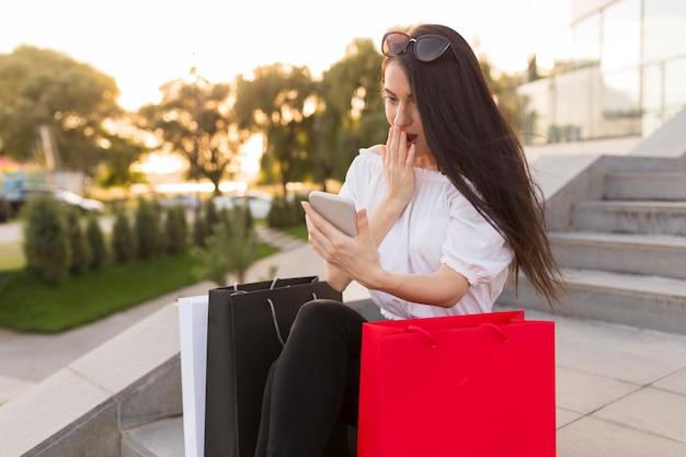 Femme choquée en regardant son téléphone
