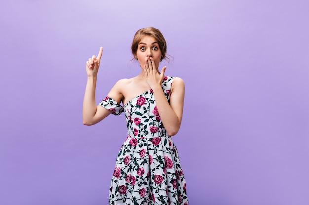 Femme choquée en robe pointant vers le haut sur fond isolé. belle fille à la mode dans des vêtements d'été colorés et lumineux a une idée cool.