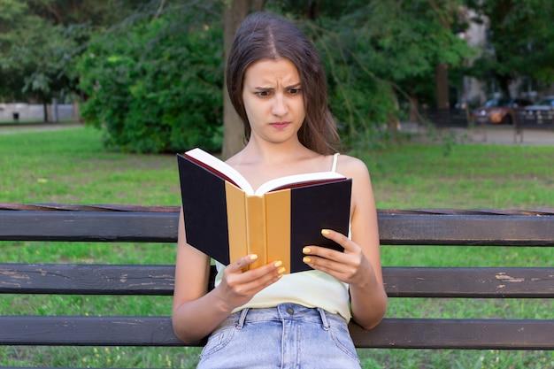 Une femme choquée et surprise tient un livre et a l'air mécontent