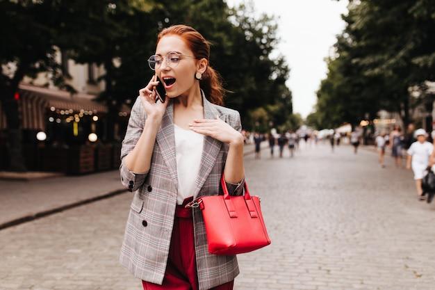 Femme choquée en veste à carreaux parlant au téléphone