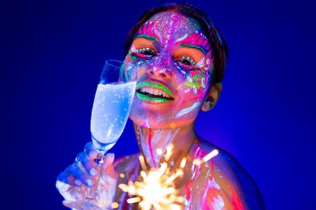 Femme avec cierge magique et coupe de champagne en néon. concept de vacances et nouvel an
