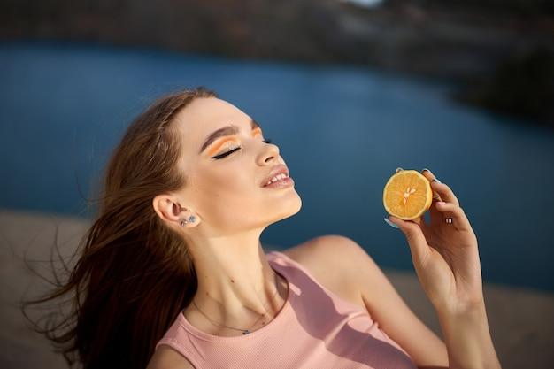 Femme avec un citron dans ses mains, nutrition de la peau de beauté avec de la vitamine c. cosmétiques naturels pour les soins de la peau du visage. ciel bleu de jour ensoleillé