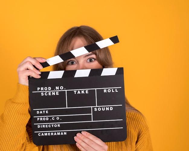 Femme avec un clap de cinéma, concept de cinéma