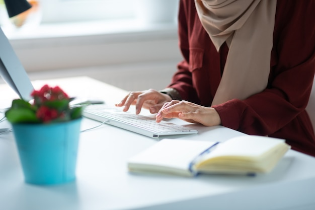 Femme et clavier. gros plan femme tapant sur le clavier alors qu'il était assis à la table avec une belle plante d'accueil