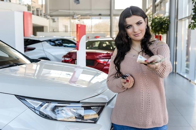 Femme avec des clés et des billets en euros debout près d'une nouvelle voiture