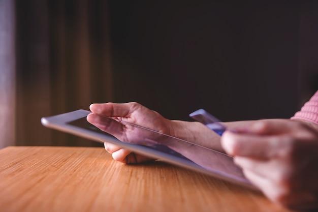 Femme client utilisant une carte de crédit et une tablette pour magasiner en ligne