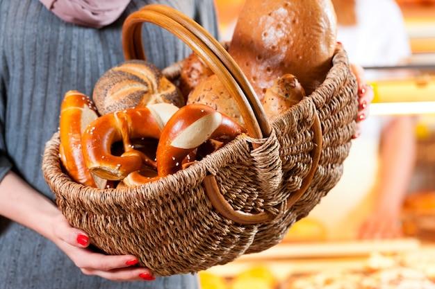 Femme cliente avec une corbeille à pain dans la boulangerie