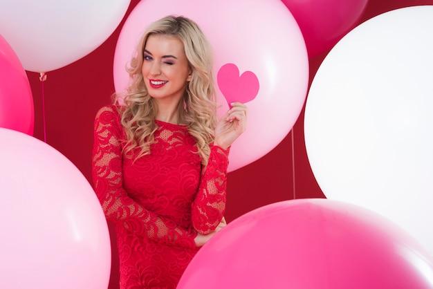 Femme clignotante avec coeur de papier rouge