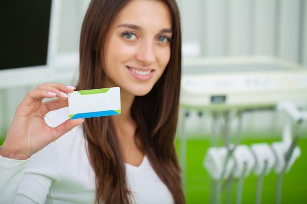Femme à la clinique dentaire détenant une carte de visite vierge