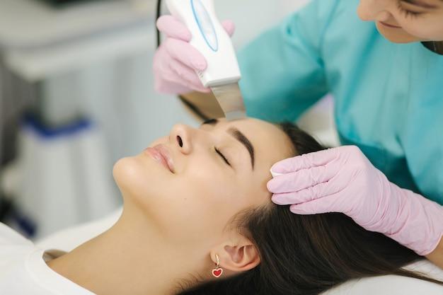 Femme à la clinique de spa de beauté cosmétique a la cosmétologie du matériel du visage. femme faisant des procédures de beauté