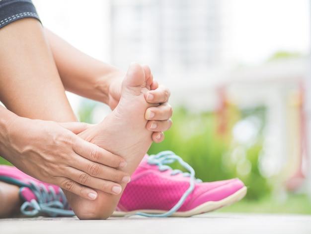 Femme closeup masser son pied douloureux pendant l'exercice. concept de blessure de sport en cours d'exécution.