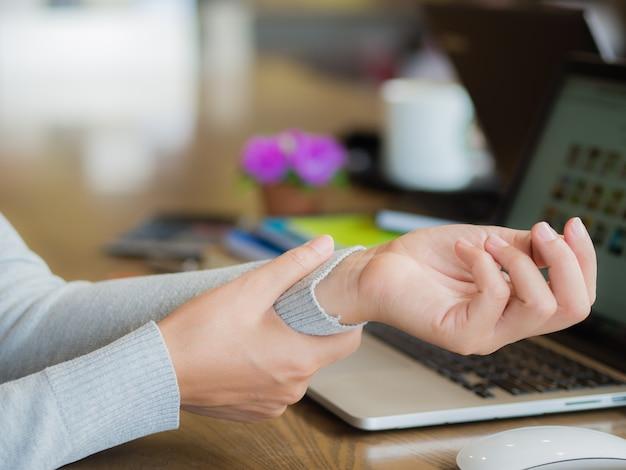 Femme closeup tenant sa douleur au poignet d'utiliser l'ordinateur depuis longtemps. syndrome de bureau concep