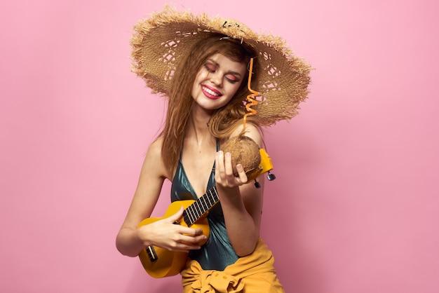 Femme avec cocktail de noix de coco dans les mains maillot de bain chapeau de plage cosmétiques mode de vie de luxe rose