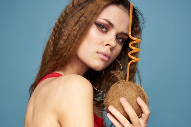 Femme avec cocktail de noix de coco en mains cheveux ondulés maquillage lumineux studio de mode de vie vacances d'été.