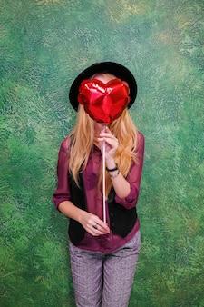 Femme avec un coeur ballon rouge le 14 février saint-valentin.