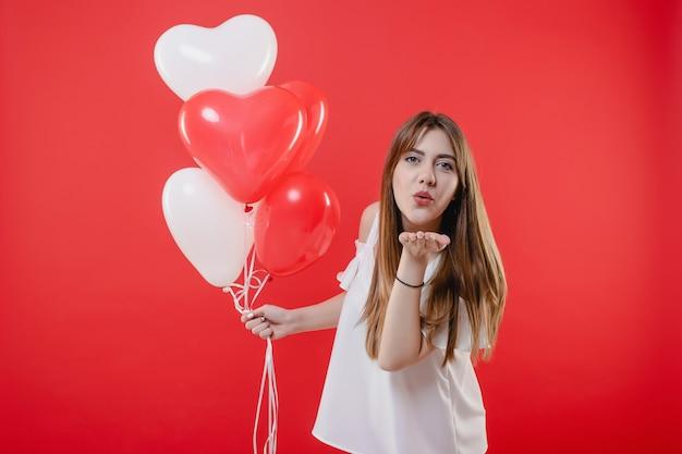 Femme, à, coeur, ballons, donner, smooch, baiser, isolé, sur, rouges