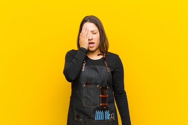 Femme coiffeur à la recherche de sommeil, s'ennuie et bâille, avec un mal de tête et une main couvrant la moitié du visage