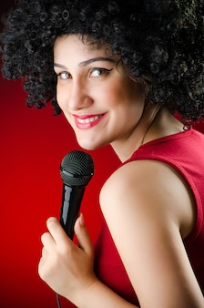 Femme avec une coiffure afro chantant au karaoké