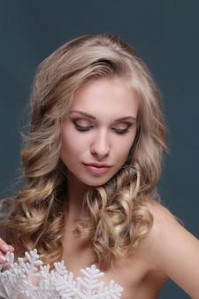Femme en coiffure blonde frisée et robe flocon de neige