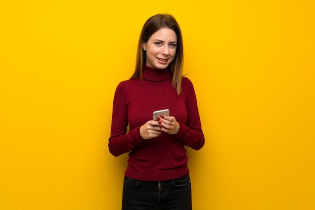 Femme avec col roulé sur un mur jaune, envoyant un message avec le téléphone portable