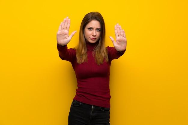 Femme avec col roulé sur un mur jaune faisant un geste d'arrêt et déçue