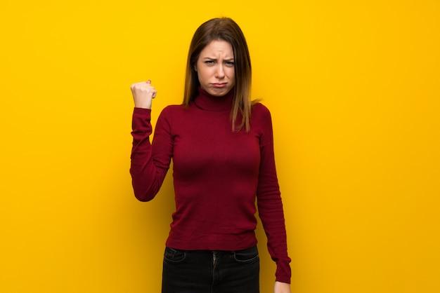Femme avec col roulé sur un mur jaune avec un geste de colère