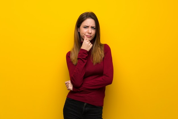 Femme, à, col roulé, sur, mur jaune, penser