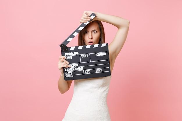 Femme en colère choquée en robe blanche couvrant le visage avec un film noir classique faisant un clap