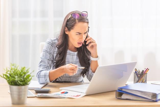 Femme en colère criant dans un téléphone portable pointant sur un ordinateur portable dans un environnement de bureau.