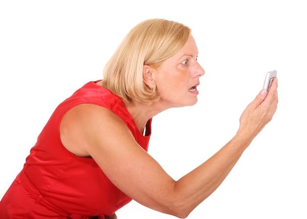 Une femme en colère criant sur son téléphone portable sur fond blanc