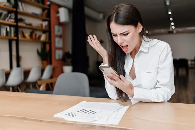 Femme en colère dans le bureau à la recherche à l'écran du téléphone avec des documents sur le bureau