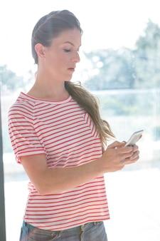Femme en colère, debout à l'intérieur d'une fenêtre, lisant son téléphone portable