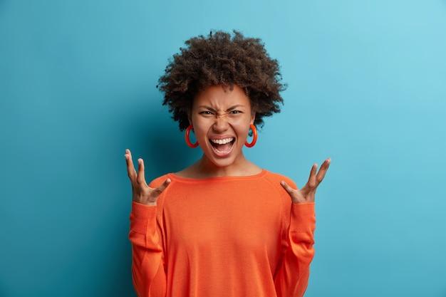 Femme en colère émotionnelle crie fort, exprime la haine et la rage, fait des gestes avec agacement, garde les mains levées de consternation, vêtue d'un pull orange, pose contre le motif bleu a une dispute avec son petit ami