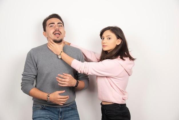 Femme en colère étouffant son petit ami de manière ludique.