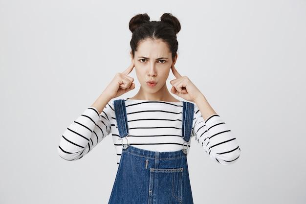 Femme en colère ferme les oreilles avec les doigts, fronçant les sourcils offensé