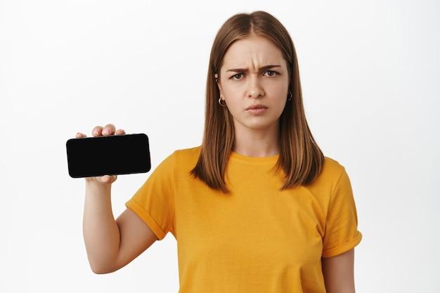 Une femme en colère montre un écran de smartphone horizontal, fronce les sourcils et a l'air contrarié par le contenu du téléphone portable, debout mécontent contre le mur blanc