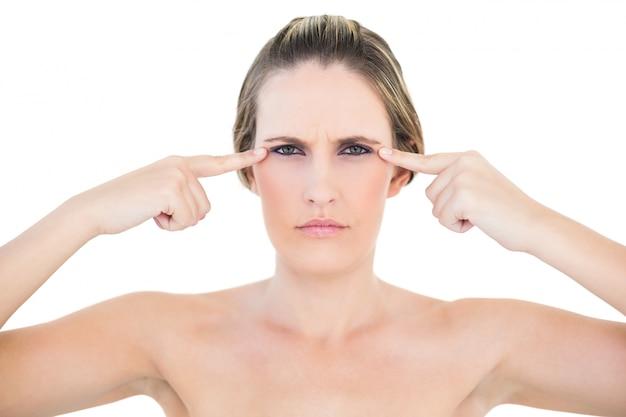 Femme en colère, pointant vers les yeux en regardant la caméra