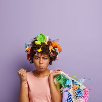 Femme en colère posant avec des ordures dans ses cheveux