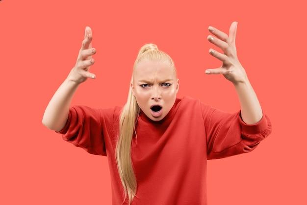 Femme en colère regardant la caméra. femme d'affaires agressive debout isolée sur fond de studio de corail à la mode. portrait de femme demi-longueur. émotions humaines, concept d'expression faciale