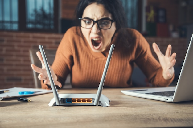Femme en colère avec routeur wifi en arrière-plan de bureau