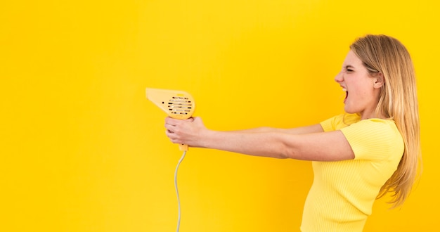 Femme en colère tenant un sèche-cheveux