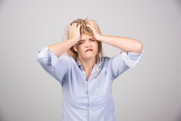 Femme en colère tirant ses cheveux sur une surface grise