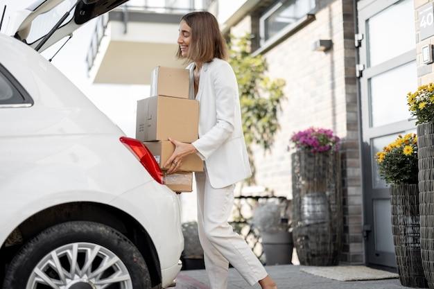 Femme avec des colis près de sa voiture et de sa maison