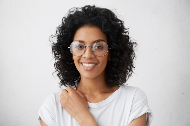 Femme de collège noire de race mixte avec une coiffure frisée souriant largement vêtue d'un chemisier blanc, à la recherche de fraîcheur et de jeunesse, portant des lunettes à la mode. émotions et sentiments humains positifs