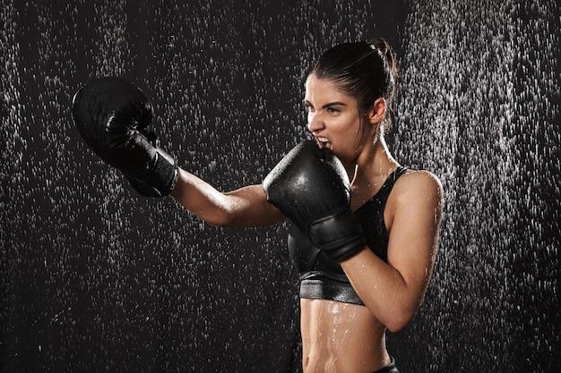 Femme combattant des années 20 en vêtements de sport et gants de boxe noirs jetant des coups de poing pendant l'entraînement sous des gouttes de pluie, isolé sur fond sombre