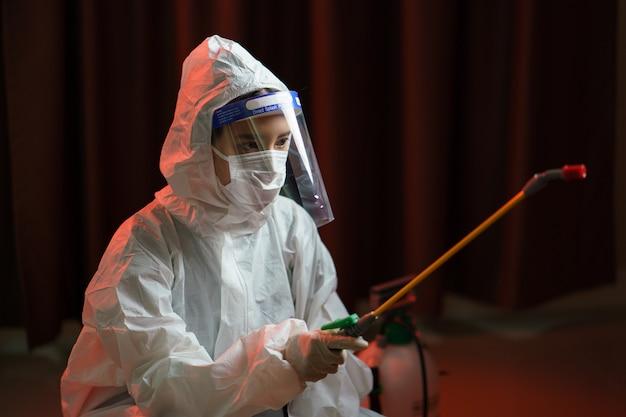 Femme en combinaison de protection contre les matières dangereuses vaporisant un désinfectant pour arrêter la propagation du coronavirus ou du covid-19.