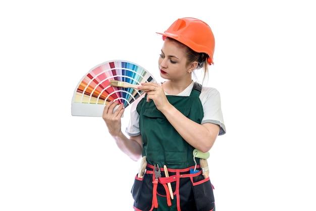 Femme en combinaison tenant un échantillon de couleur et un pinceau isolé