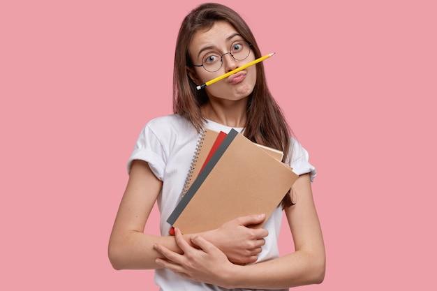 Une femme comique bouleversée fait la grimace, garde un crayon sur la bouche, s'ennuie d'étudier seule, porte des blocs-notes