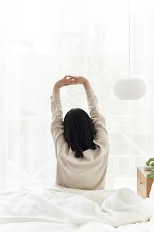 Femme commençant sa matinée avec un étirement